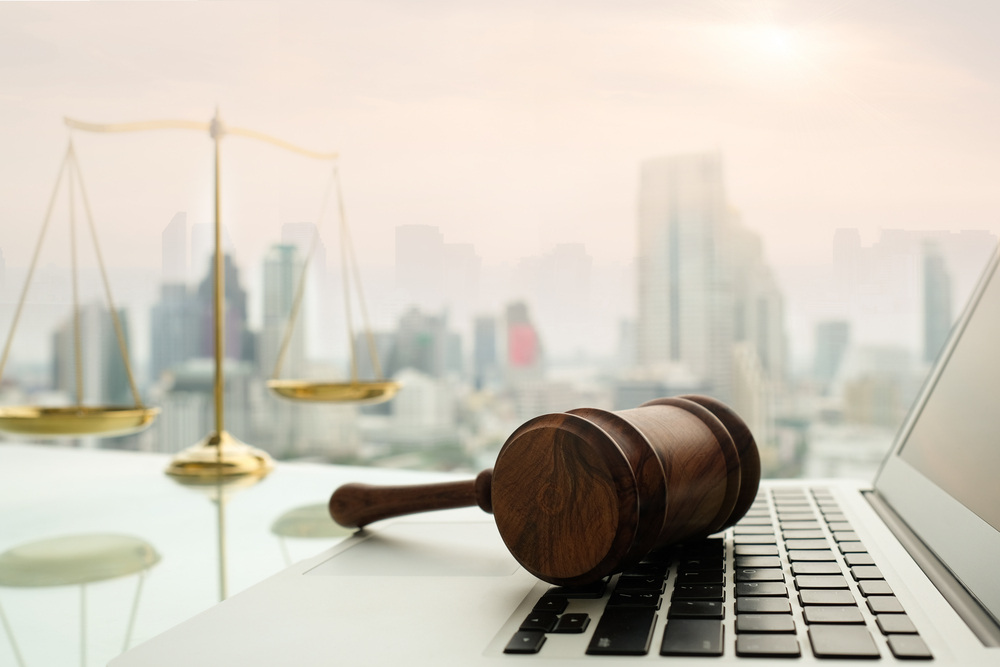 Gavel on a laptop with justice scale and cityscape in background.