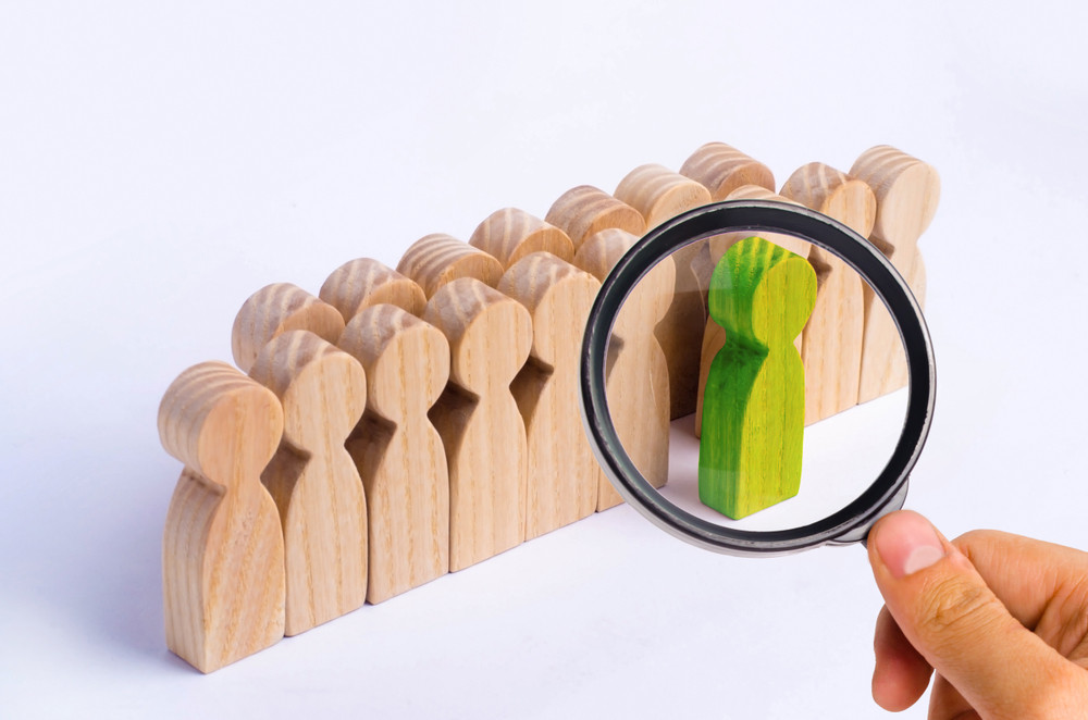 Wooden human figures standing in a line with one painted in green standing in front of the crowd with magnifying glass focused on it.