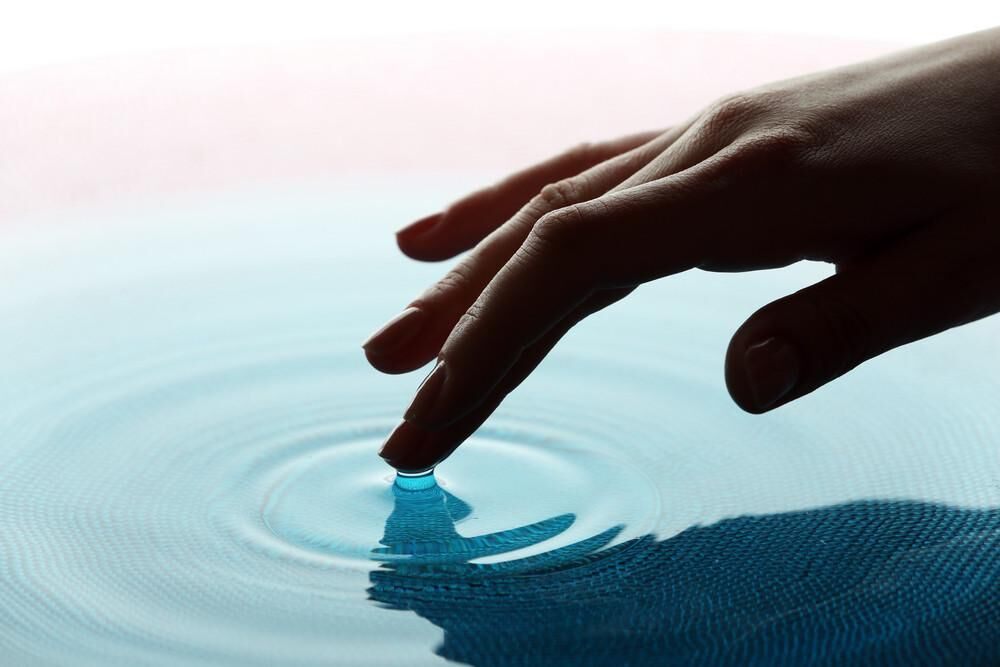 Image of a hand touching smooth teal colored water.