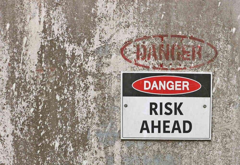 "An old cement wall with a sign plastered on it that says ""Danger""."