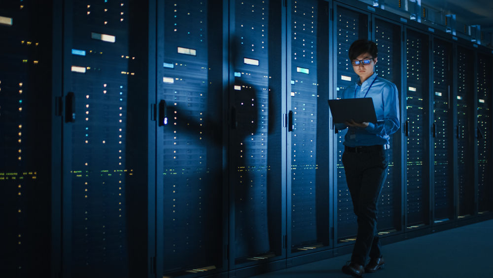 A professional monitoring a series of large, dark mainframe computers.