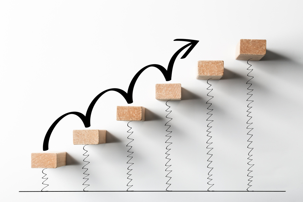 Concept of growth using a sequence of blocks forming stairs with an arrow.